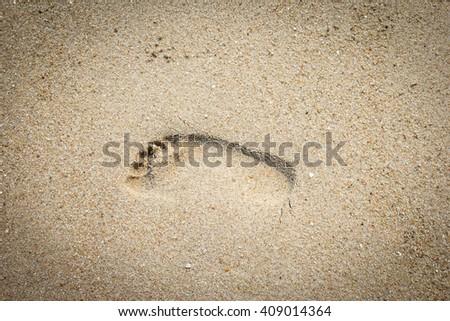 Foot prints on a sandy beach - stock photo