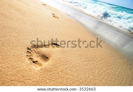 Foot Prints on Tropical Sandy Beach and sea waves in the background - stock photo