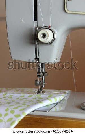 Foot sewing machine with a needle and cloth.