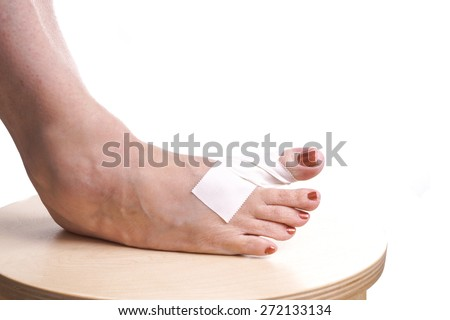 Foot with Therapeutic self adhesive tape on a Foot because  the Foot is hurt by a Sports Injury or arthritis pain - stock photo