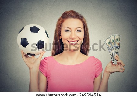 Football and money. Young attractive woman holding soccer ball and cash isolated on grey wall background. Competition lottery gambling concept idea - stock photo