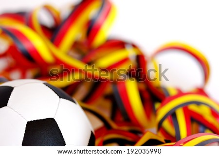 Football and streamers in black, red, yellow - stock photo