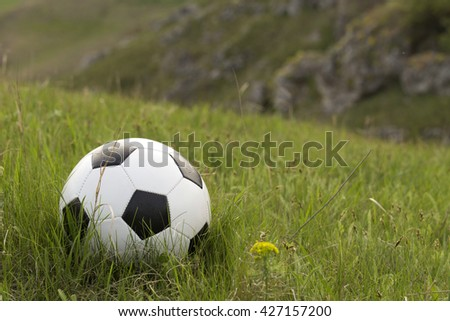 Football and the green hill. Ball is situated on the grass. - stock photo