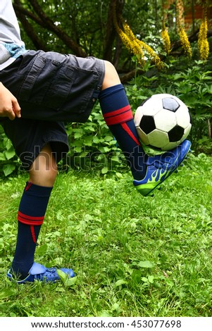 football ball and legs in soccer boots close up photo on the green lawn background - stock photo