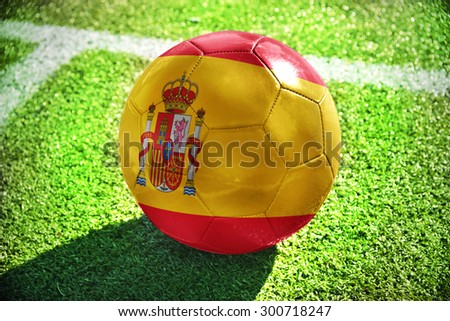 football ball with the national flag of spain lies on the green field near the white line