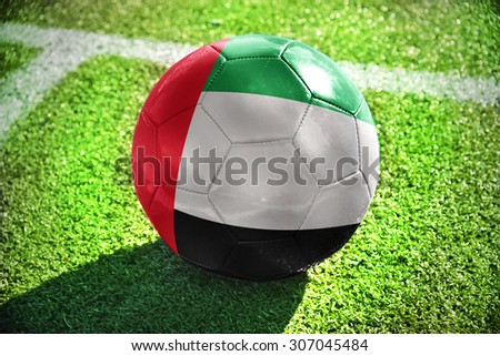 football ball with the national flag of united arab emirates lies on the green field near the white line