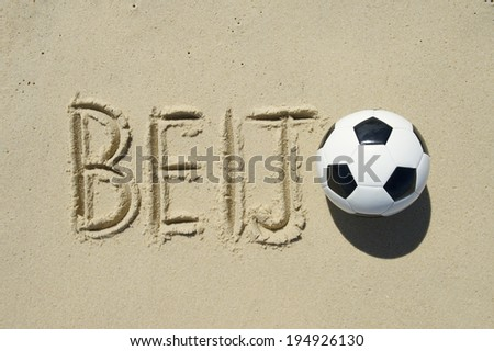 Football beijo (kiss in Portuguese) message with a soccer ball handwritten in sand - stock photo