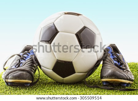 Football black and white over green grass, with football shoes, horizontal hdr image - stock photo