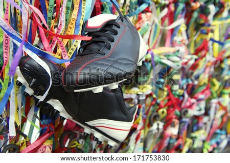 Football boots soccer cleats hanging with Brazilian wish ribbons at the Bonfim church in Salvador Bahia Brazil - stock photo