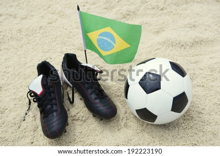 Football boots with soccer ball and Brazilian flag on sand beach background - stock photo