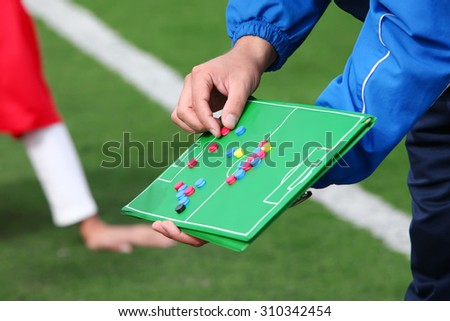 Football coach gives directions to players on desk - stock photo