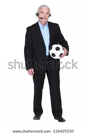 Football commentator holding ball - stock photo