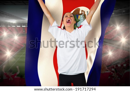 Football fan in white cheering holding costa rica flag against vast football stadium with fans in red - stock photo
