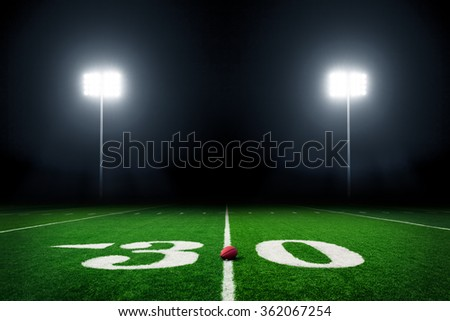 Football field at night with stadium lights - stock photo