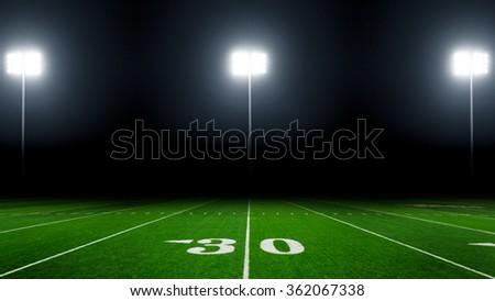 Football field at night with stadium lights, 16x9 aspect ratio - stock photo