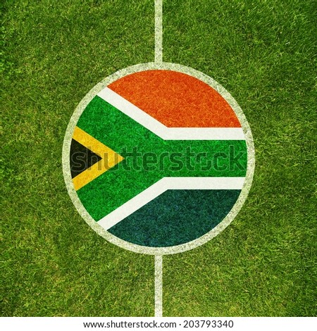 Football field center closeup with South African flag in circle  - stock photo