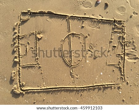 Football field drawing on sand beach.