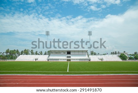 football field with green grass and lamp posts - stock photo