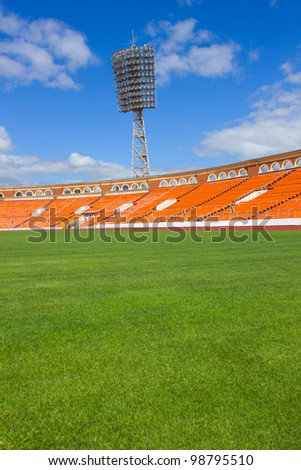 football field with light stand and orange seats - stock photo