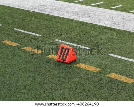 Football Field Yard Marker - Ten 10 yard line on turf playing field  - stock photo