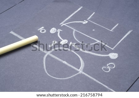 Football game tactical plan for attacking: Hand drawing with chalk on the black project paper - stock photo