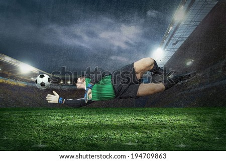 Football golkeeper with ball in action under rain in stadium