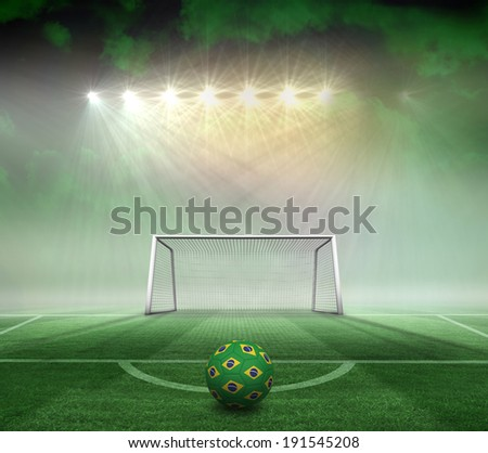 Football in brazilian colours against football pitch and goal under spotlights - stock photo
