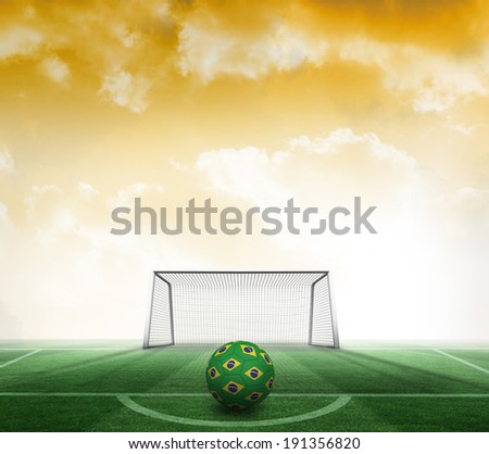 Football in brazilian colours against football pitch and goal under yellow sky - stock photo