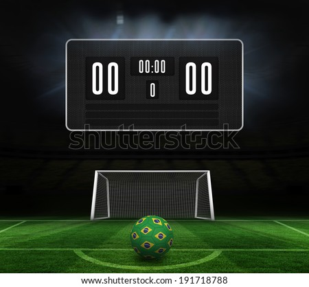Football in brazilian colours and scoreboard against football pitch and goal under spotlights - stock photo