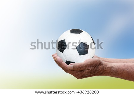 Football in human hands.Blur the background of sky and grass