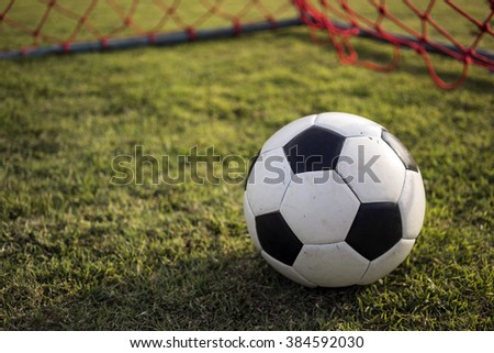 Football inside red goal net on the green grass field, inside view 3 - stock photo