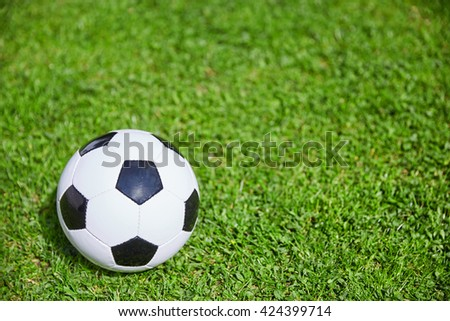 Football lying on the green grass of the soccer field