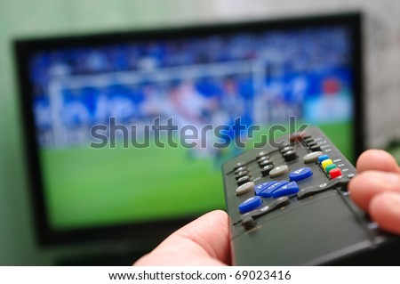 Football match and remote control - stock photo