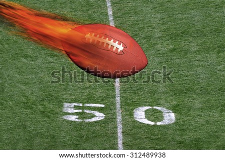 Football on fire crossing the fifty yard line.. - stock photo