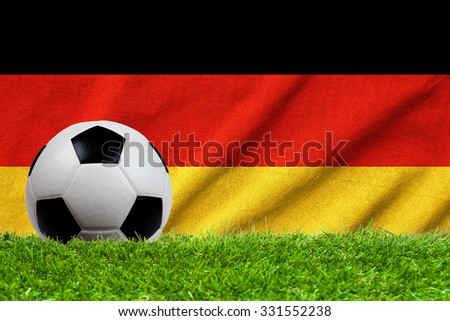 Football on grass field with wave flag of Germany - stock photo