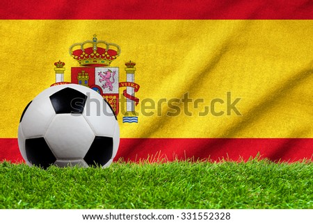 Football on grass field with wave flag of Spain