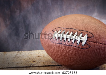 Football on old ages wood table and studio tan and blue back drop with copy space - stock photo