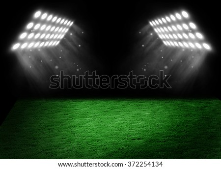 Football on the stadium lawn, shined with light of searchlights