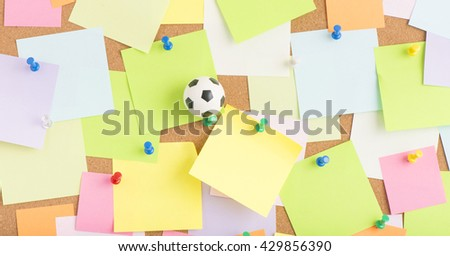 Football or soccer ball and blank sticky notes on notice board in office. Concept image of business related sport and leisure. Reminder of summer vacation and games. - stock photo