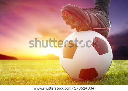 Football or soccer ball at the kickoff of a game with sunset - stock photo
