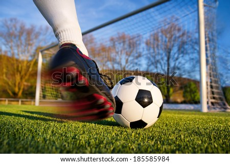 Football or soccer shot with a neutral design ball being kicked, with motion blur on the foot and natural background - stock photo