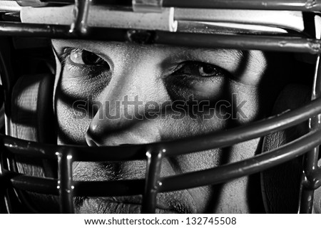 Football Player -  A young man with a mean look wearing a football helmet. This is a high contrast processed black and white image to enhance texture. - stock photo