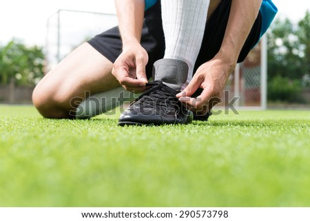 Football player getting ready for the game tying his shoes. background sunset - stock photo