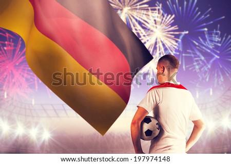 Football player holding the ball against fireworks exploding over football stadium - stock photo