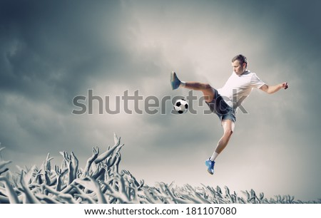 Football player in jump kicking the ball supported by fans