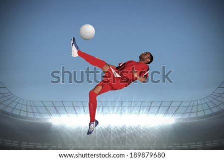 Football player in red kicking against large football stadium with spotlights under grey sky