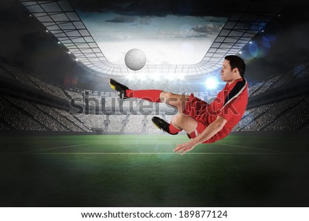 Football player in red kicking in a large football stadium with lights