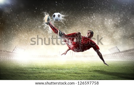 football player in red shirt striking the ball at the stadium under rain - stock photo