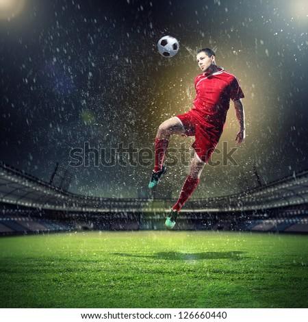 football player in red shirt striking the ball at the stadium under rain - stock photo
