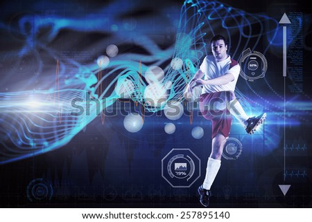 Football player in white kicking against abstract glowing black background - stock photo